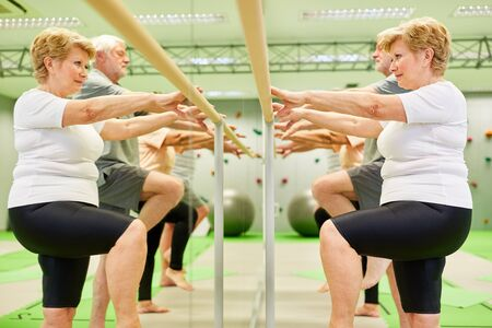 Senior group trains motor skills and coordination at the ballet bar in physiotherapy Stock Photo
