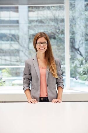 Cheerful young business woman as start-up founder in the office