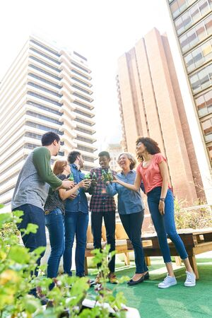 Start-Up Team celebrates a party on a rooftop or roof garden in the city