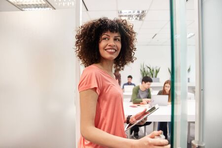 Cheerful african business woman as an intern or trainee in coworking office