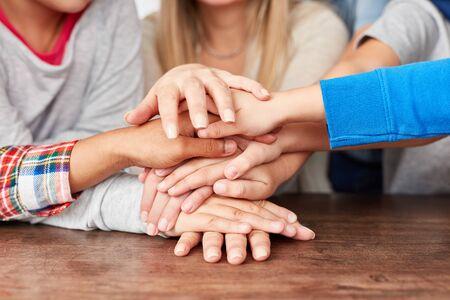 Viele Kinder stapeln Hände als Kooperations- und Freundschaftskonzept