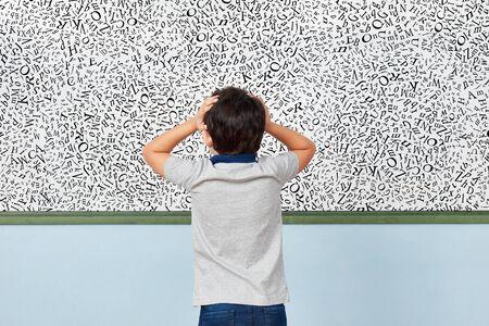 Kind mit Legasthenie steht in der Grundschule vor einem Whiteboard mit vielen Buchstaben