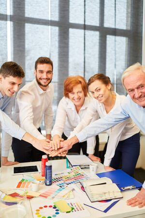 Successful team of designers stack their hands together with joy