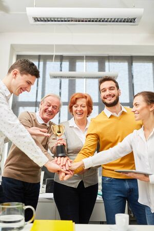 Start-up team stapelt handen op elkaar als winnaars met trofee Stockfoto