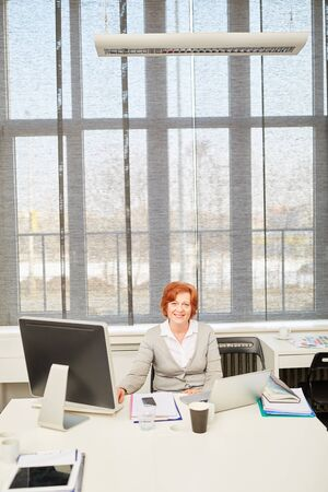 Senior business woman with experience at her place of work in the office 版權商用圖片