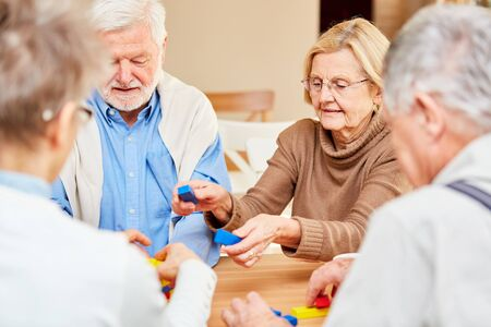 Senior group plays with colorful building blocks in a dementia therapy at retirement home