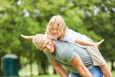 Blond boy balances on the back of his father in the garden in summer