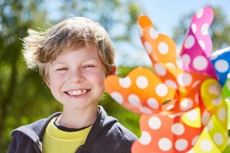 Naughty smiling boy with a colorful pinwheel in summer in the sunshine Stock Photo