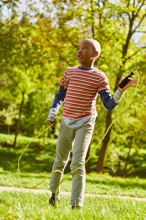 Niño africano está jugando con la cuerda de saltar en el parque en las vacaciones de verano