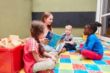 Children group and kindergarten teacher reading a children's book