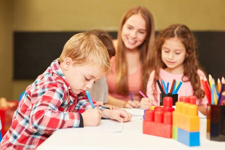 Boy paints with colored pencils in the painting class of the day care center or preschool