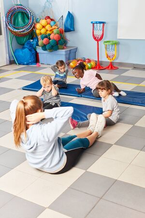 Group of kids does gymnastics together with sports teacher in the gym of the school Stock Photo