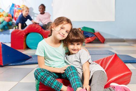 Two girls hug each other as best friends at the children's sport in kindergarten