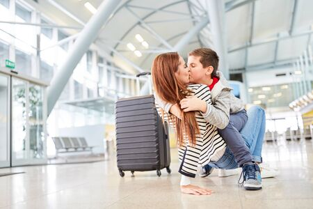 Son hugs and kisses his mother while picking up after a trip at the airport terminal