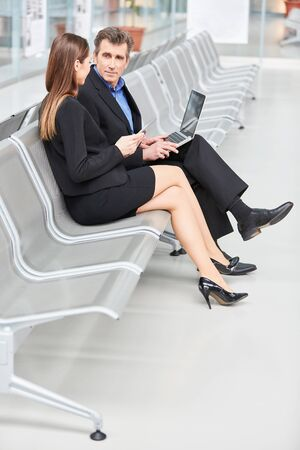 Two business people in the airport together plan the business trip with laptop computer