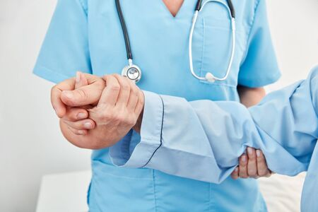 Hands of caregiver support hand of frail patient in nursing home