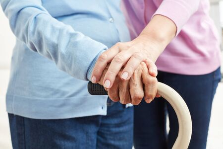 Hand of a young woman touches hand of a senior citizen as comfort and caring 스톡 콘텐츠