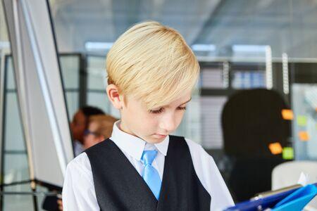 Als Geschäftsmann oder Berater verkleideter Junge liest ein Dokument im Büro