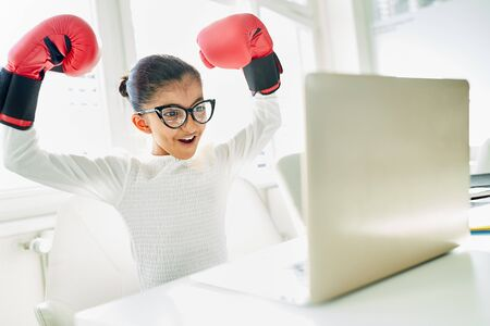 Girl as a business woman with boxing gloves while cheering at laptop computer