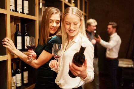 Two young women look at a bottle of red wine during the wine tasting