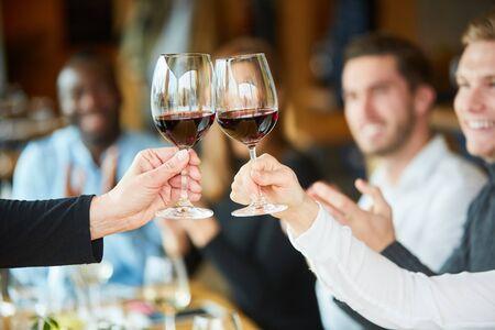 Los amigos celebran una fiesta juntos en el restaurante y brindan con vino tinto