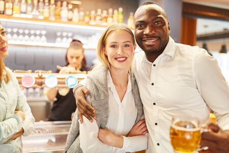 Multicultural Couple Dating in a Pub or Bar Drinking Beer