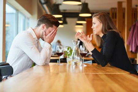 Young couple arguing about jealousy in the restaurant over a glass of wine