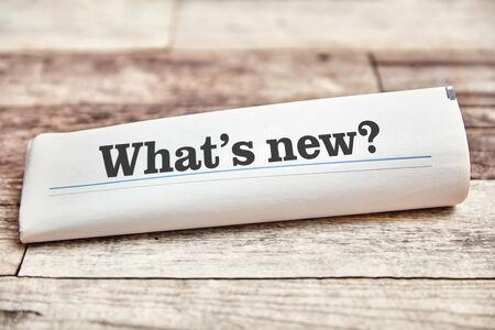 Quoi de neuf comme titre d'un journal plié sur une table en bois