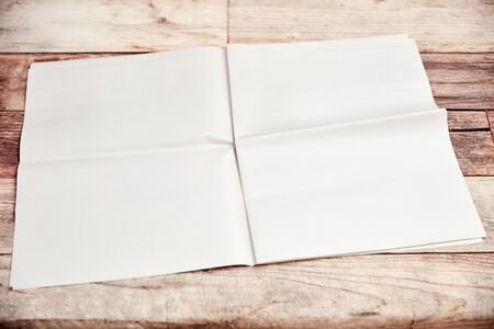 Open newspaper with blank unprinted pages lies on wood 免版税图像