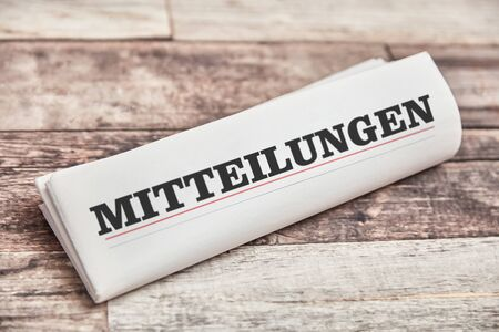 """German word """"Mitteilungen"""" (messages) in the title as a folded newspaper"""