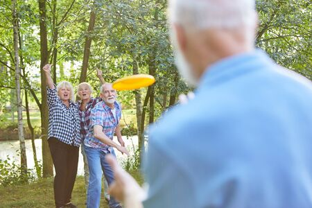 Seniors enjoy playing Frisbee game in summer on vacation in the garden