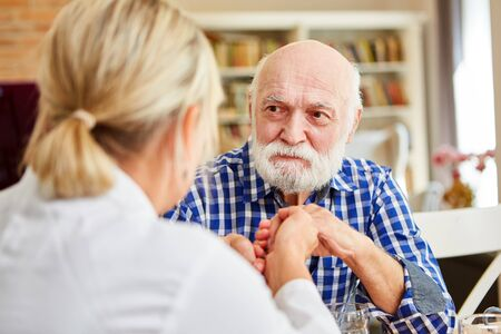 Doctor or nursing wife consoles demented senior on home visit