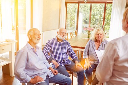 Seniors talking in group psychotherapy with therapist in nursing home Stock Photo