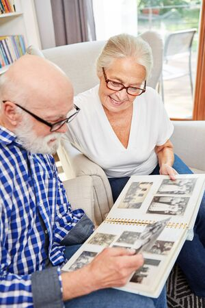 Happy seniors couple is looking at old family photos in photo album indoors