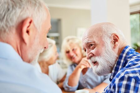 Seniors as friends talk to each other in the lounge in the retirement home
