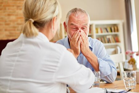 Weeping senior man as a patient with grief and a doctor on home visit