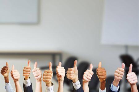 Ręce w sali konferencyjnej trzymają kciuki w górę