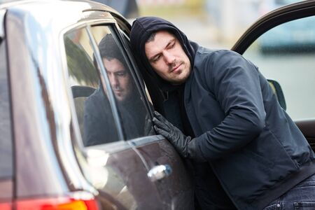 Man as a thief at the open door of a car