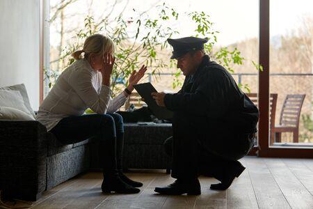 Psicólogo de la policía hablando con una víctima tras un robo con allanamiento de morada Foto de archivo