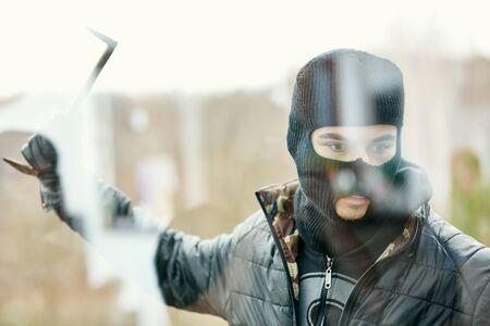 Cambrioleur avec pied de biche veut frapper les fenêtres lors de l'effraction