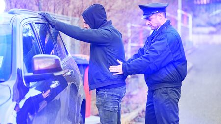 Policeman in the blue light of a civil stripe on search and arrest of a car thief
