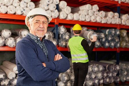 Senior as a confident warehouse worker with crossed arms in the warehouse Banque d'images