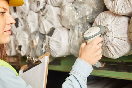 Une femme en tant que spécialiste d'entrepôt avec liste de contrôle et scanner inspecte l'inventaire