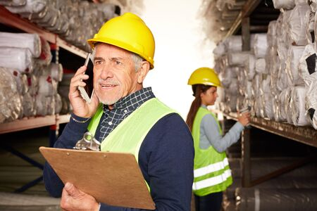 Old logistics worker is phoning with the smartphone in the carpet warehouse