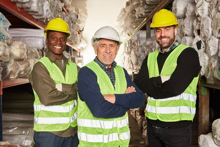 Three warehouse workers proudly stand in a warehouse with their arms crossed