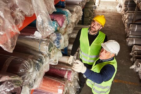 Two warehouse workers in the carpet warehouse make delivery together for shipping