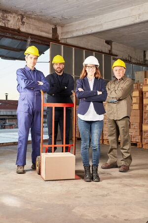 Logistics team with parcel and hand truck in warehouse by mail order Stockfoto