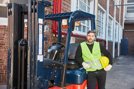 Man as forklift driver with forklift in front of the warehouse in the logistics center Stockfoto