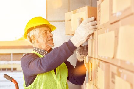 Senior warehouse worker in warehouse at parcel delivery for shipping