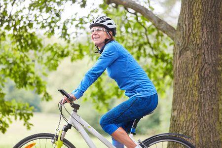 Vital senior woman makes a bike tour on a mountain bike in nature Stockfoto